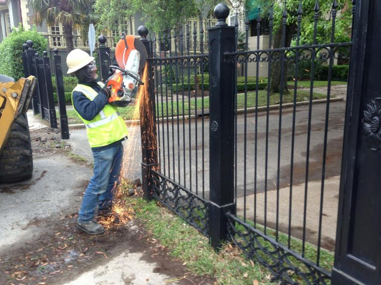 A worker cuts through the Newcomb Boulevard fence Tuesday morning.