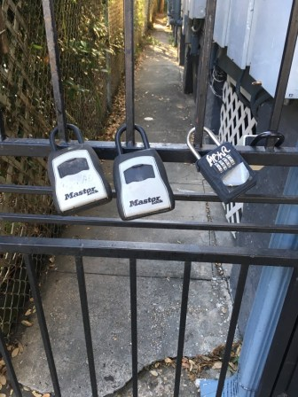 Multiple lockboxes on an alleyway gate are often a sign of short-term rental activity.
