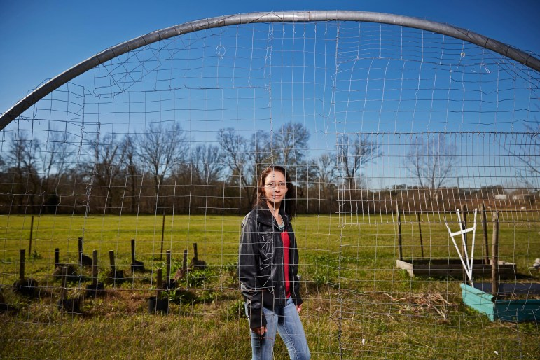 Chief Shirell Parfait-Dardar, of the Grand Caillou/Dulac Band of Biloxi-Chitimacha-Choctaw Indians, stands behind the trellis for her green beans, made of old trampoline parts.