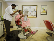"""Gail Brooks takes in the day's news  while Wilbert """"Mr. Chill"""" Wilson cuts her hair at the shop bearing his nickname on South Carrollton Avenue. Wilson said he owes his success to the paper, which has featured community events held at his shop. For instance, the paper wrote a feature story in 2010 when Mayor Mitch Landrieu and others came to the barber shop to teach young men how to tie a tie and pass on other tips from generation to generation."""