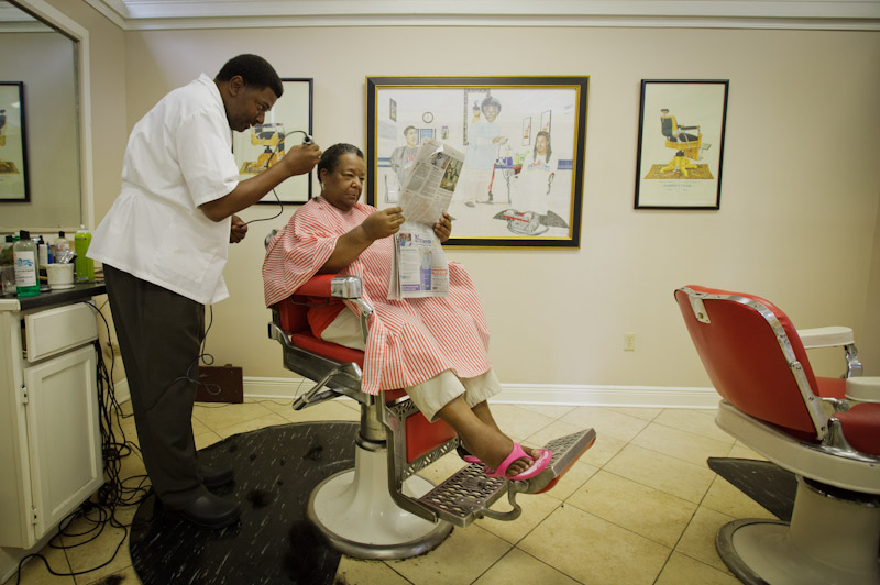 "Gail Brooks takes in the day's news  while Wilbert ""Mr. Chill"" Wilson cuts her hair at the shop bearing his nickname on South Carrollton Avenue. Wilson said he owes his success to the paper, which has featured community events held at his shop. For instance, the paper wrote a feature story in 2010 when Mayor Mitch Landrieu and others came to the barber shop to teach young men how to tie a tie and pass on other tips from generation to generation."