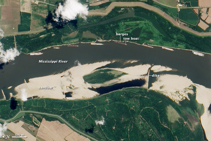 During a drought in August 2012, a towboat and barges ran aground on the Mississippi River near Greenville, Miss. This satellite image (rotated so that north is to the left) shows a large sandbar on the western side of the river. Strings of barges, each up to 1,000 feet long, anchored on the east side of the river, wait for clearance to move north or south. In a drought like this, no one has the authority to determine which would have priority on the river: shipping or sediment diversions to rebuild the coast.