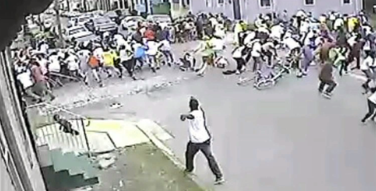This image from a surveillance video shows people scattering as a man shoots into the crowd at a second-line parade Sunday.