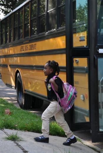Kindergartner Am'marie Watkins walks off the bus at John Dibert Community School, one of the charter schools that takes kids from around the city. FirstLine Schools, Dibert's operator, also handles busing for the Recovery School District's direct-run schools.