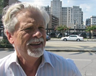 Standing on Canal Street, Pres Kabacoff describes his ideas to redevelop downtown New Orleans. The parking lot across the street would become a new mall to rival Lakeside Shopping Center. The old Charity Hospital, in the background, would be the home to City Hall, Civil District Court and a neuroscience research center.