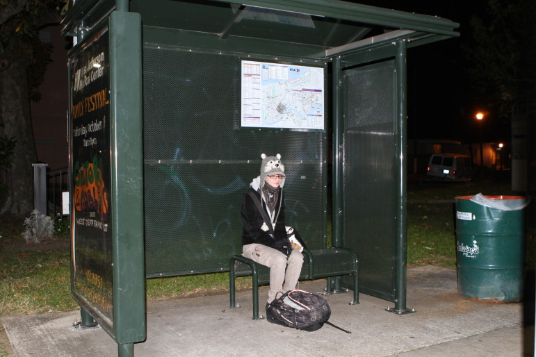 Amelia Slep-Patterson waits for the bus in Algiers at the start of her long trip to school. Between the dark bus stop and the early-morning walk down Canal, she said she has to on guard.