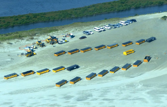 A caravan of loaders testifies to the size of the BP oil that has been uncovered near Fourchon Beach in recent weeks