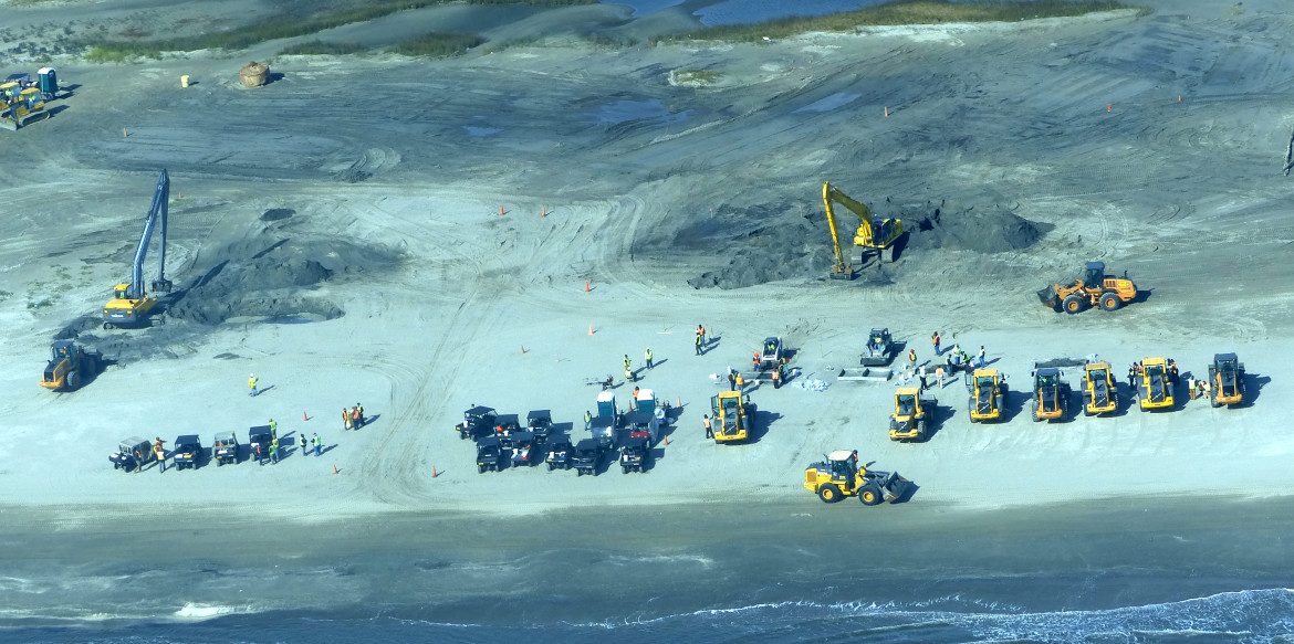 Heavy equipment digs into Fourchon Beach searching for more of the massive oil mats left  by the Deepwater Horizon disaster in 2010.
