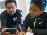 Using an app that scans an English text and translates it into Spanish, Ramon Leon helps his son with homework at the VAYLA office in eastern New Orleans.