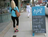 A sign at Azby's, a women's clothing store on Magazine, exhorts people to shop local. On the next block is Chico's, a national women's clothing chain.