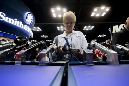 A woman holds a revolver in the exhibit hall at the NRA's annual convention in Indianapolis.