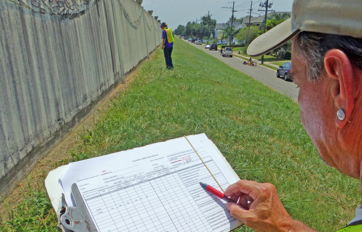 Johnny Holzenthal consults a checklist while walking the Orleans Outfall Canal during a quarterly inspection of the metro area's new hurricane protection system. Before Hurricane Katrina, local levee boards often ignored federal rules requiring regular inspections, but today the Southeast Louisiana Flood Protection Authority has 11 people doing checks full-time.