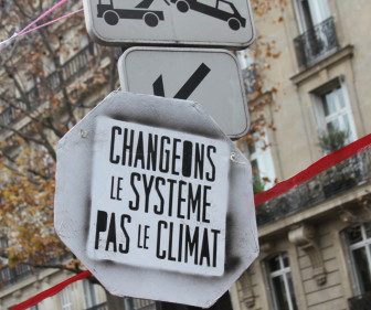 Activists in Paris rallied to a slogan urging the world to change the system, not the climate. The red ribbon symbolized a line negotiators were urged not to cross.