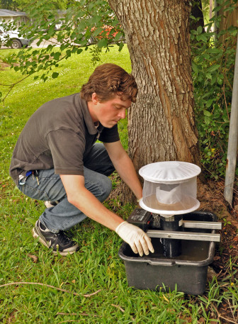 Brendan Carter of the New Orleans Mosquito, Termite and Rodent Control Board sets a mosquito trap in Gentilly.