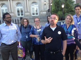 Theater teacher Terry Marek and other members of United Teacher of Lusher speak to reporters after walking out of the ballot counting.