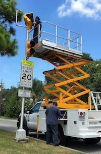 city workers reprogram school zone light
