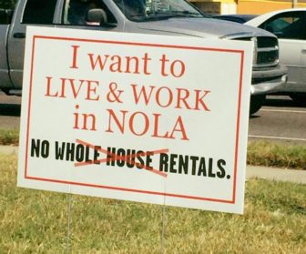 A yard sign links short-term, whole-house rentals to the lack of affordable housing in New Orleans.