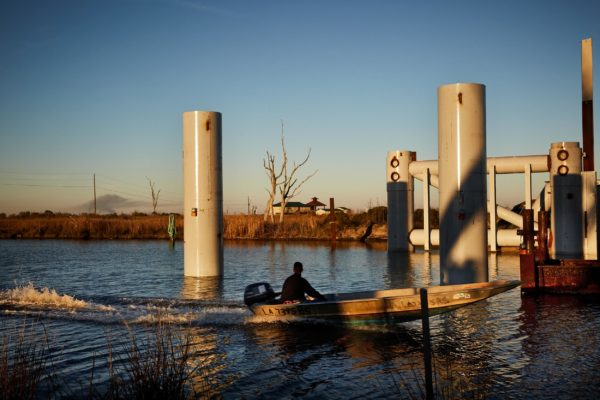 A boater passes a floodgate under construction in Bayou Pointe-aux-Chenes.