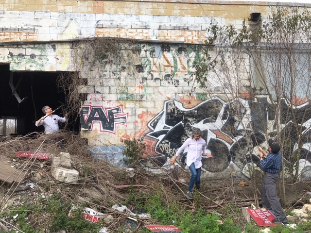 The author (middle) and colleagues clear away trash and underbrush to get a better look at the mural.
