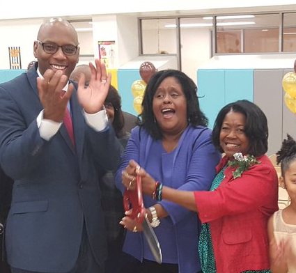 Moton CEO and Principal Paulette Bruno (center) cuts the ribbon for Moton's new building with schools Superintendent Henderson Lewis Jr. (left) at a dedication ceremony in December 2016. Bruno has been fighting nepotism charges for five years.